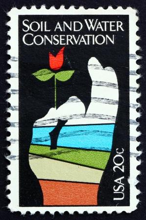 conservacion del agua: ESTADOS UNIDOS DE AMERICA - CIRCA 1984: un sello impreso en los EE.UU. muestra la flor en la mano Conservaci�n, Suelo y Agua, circa 1984 Editorial
