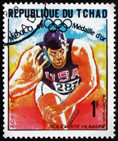 lancio del peso: CIAD - CIRCA 1969: un francobollo stampato in Ciad mostra Randy Matson, Lancio del peso, atletica leggera, vincitore del 1968 Giochi Olimpici, Messico, circa 1969 Editoriali