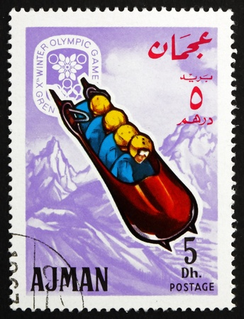 bobsled: AJMAN - CIRCA 1967: a stamp printed in the Ajman shows Four-man Bobsled, Winter Olympics 68, Grenoble, circa 1967 Editorial