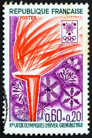 flambeau: FRANCE - CIRCA 1968: a stamp printed in the France shows Olympic Flame and Snowflakes, 10th Winter Olympic Games, Grenoble 68, circa 1968