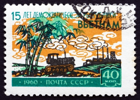 RUSSIA - CIRCA 1960: a stamp printed in the Russia shows Tractor and Factory, 15th Anniversary of North Vietnam, circa 1960 Stock Photo - 20511183