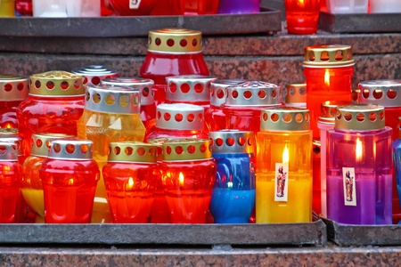 Lot of illuminated votive candles glows on a grave photo
