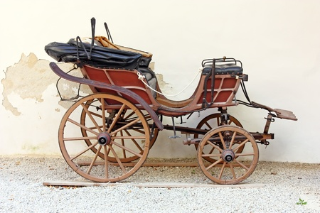 Old wooden carriage in front of wall photo
