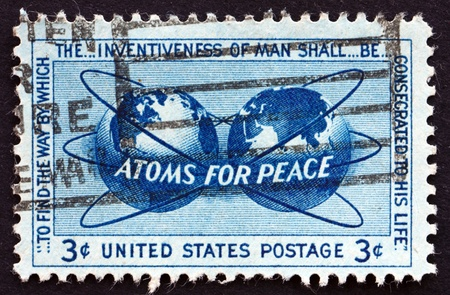 encircling: UNITED STATES OF AMERICA - CIRCA 1955: a stamp printed in the USA shows Atomic Energy Encircling the Hemispheres, Atoms for Peace Policy, circa 1955 Editorial