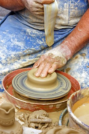 Close up of potters hands making clay pot photo
