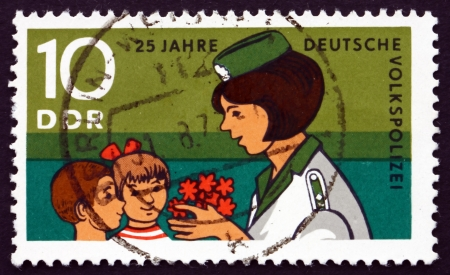 pioneers: GDR - CIRCA 1970: a stamp printed in GDR shows Young Pioneers Congratulating Police Woman, 25th Anniversary of the People's Police, circa 1970 Editorial