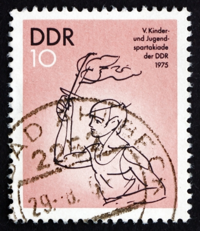 bearer: GDR - CIRCA 1975: a stamp printed in GDR shows Torch Bearer, 5th Children and Youths Spartakiad, circa 1975