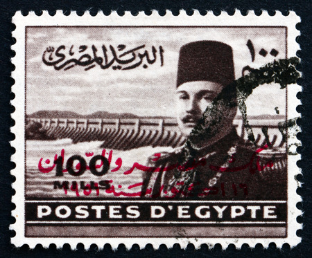 farouk: EGYPT - CIRCA 1949: a stamp printed in Egypt shows King Farouk of Egypt and Aswan Dam, circa 1949 Editorial