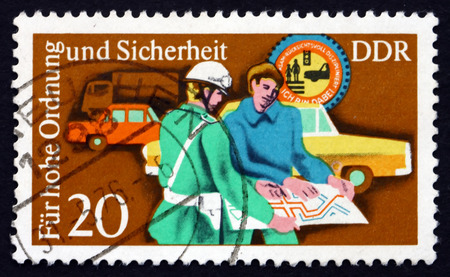 ddr: GDR - CIRCA 1975: a stamp printed in GDR shows Policeman Helping, Motorist, Traffic Police Serving and Instructing the Public, circa 1975 Editorial