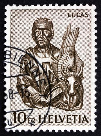 ルーク: SWITZERLAND - CIRCA 1961: a stamp printed in the Switzerland shows St. Luke and Winged Ox, 15th Century Wood Carving from St. Oswald�s Church, Zug, circa 1961