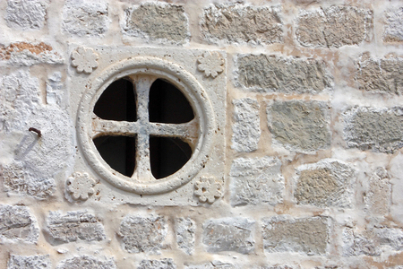 Round window without casements on the stone wall photo