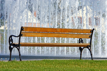 Empty wooden bench in the park in front of the fountain photo