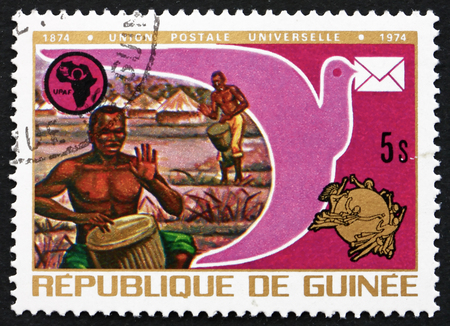 upu: GUINEA - CIRCA 1974: a stamp printed in the Guinea shows Drummers, Pigeon, UPAF and UPU Emblems, Centenary of Universal Postal Union, circa 1974