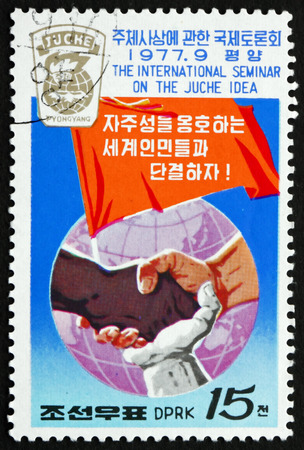 NORTH KOREA - CIRCA 1977: a stamp printed in North Korea shows Joined Hands of Different Races, Banner and Globe, circa 1977