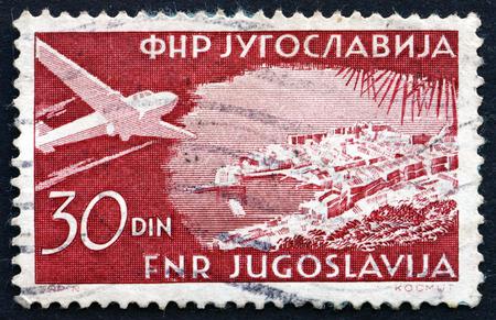 YUGOSLAVIA - CIRCA 1951: a stamp printed in the Yugoslavia shows Plane over Dubrovnik, Croatia, circa 1951