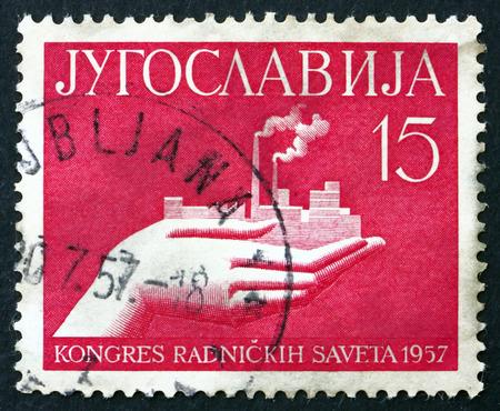 councils: YUGOSLAVIA - CIRCA 1957: a stamp printed in the Yugoslavia shows Hand Holding Factory, Congress of Workers' Councils, Belgrade, circa 1957