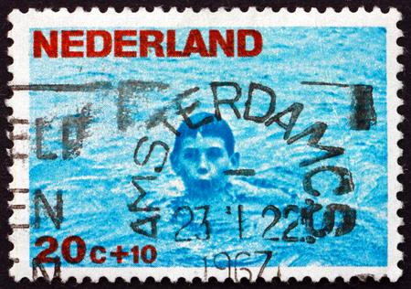 natation: PAÍSES BAJOS - CIRCA 1966: un sello impreso en los Países Bajos muestra la natación del muchacho, alrededor del año 1966