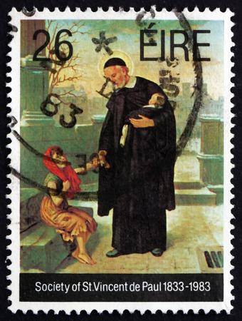 sacerdote: IRLANDA - CIRCA 1983: Un sello impreso en Irlanda muestra Sacerdote y Ni�os, Sociedad de San Vicente de Pa�l, Sesquicentenario, Organizaci�n Cat�lica Voluntario, alrededor de 1983 Editorial