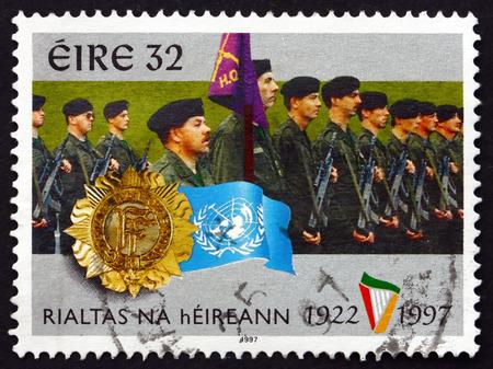 un used: IRELAND - CIRCA 1997: A stamp printed in Ireland shows Irish Defense Forces, Badges and UN Flag, circa 1997 Editorial