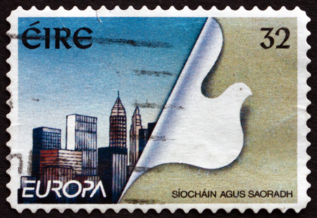 reconstructed: IRELAND - CIRCA 1995: A stamp printed in Ireland shows Stylized Dove and Reconstructed City, Peace and Freedom, circa 1995 Editorial