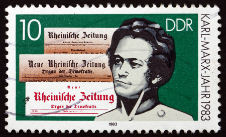 sociologist: GERMANY - CIRCA 1983: a stamp printed in Germany shows Karl Marx and Newspaper Mastheads, circa 1983