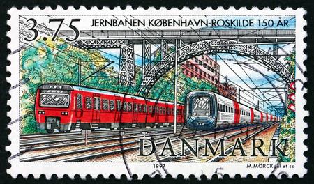 carlsberg: DENMARK - CIRCA 1997: a stamp printed in Denmark shows Two Modern Trains under Carlsberg Bridge, Copenhagen-Roskilde Railway, 150th Anniversary, circa 1997
