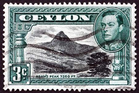 adams: SRI LANKA - CIRCA 1938: a stamp printed in Sri Lanka shows View of Adams Peak and Portrait of King George VI, circa 1938