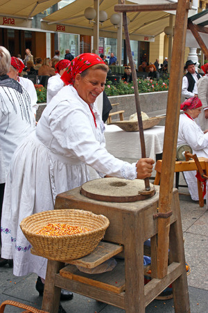 millstone: CROATIA ZAGREB  21 SEPTEMBER 2013: Woman dressed in traditional clothes grinds flour, Croatia Editorial