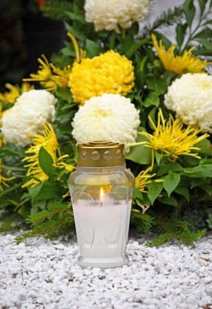 glows: Flowers and votive candle which glows on the grave, lantern