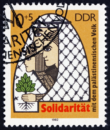 arbol de problemas: GERMANY - CIRCA 1982: a stamp printed in Germany shows Palestinian Family and Tree of Life, Palestinian Solidarity, circa 1982
