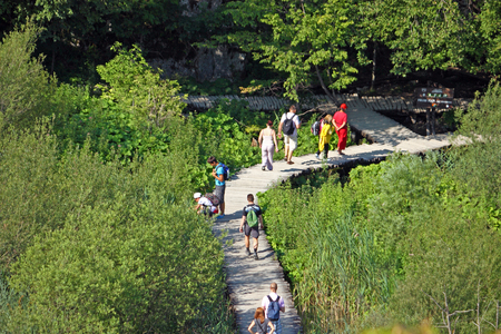 unesco: CROATIA PLITVICE, 16 JULY 2011: Tourists walk on a path in Plitvice Lakes National Park, Croatia