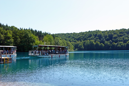 unesco: CROATIA PLITVICE, 16 JULY 2011: Beautiful lake with river boats on the blue water Editorial