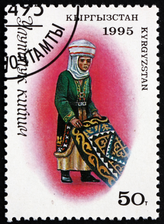 KYRGYZSTAN - CIRCA 1995: a stamp printed in the Kyrgyzstan shows Woman in Traditional Kyrgyz Costume with Carpet, circa 1995