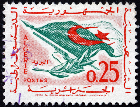 ALGERIA - CIRCA 1963: a stamp printed in Algeria shows flag, rifle and olive branch, circa 1963 Sajtókép