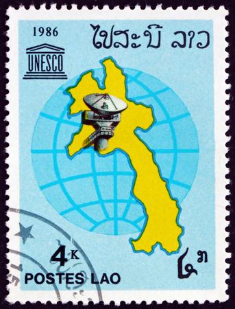LAOS - CIRCA 1986: a stamp printed in Laos shows satellite dish, map and globe, circa 1986