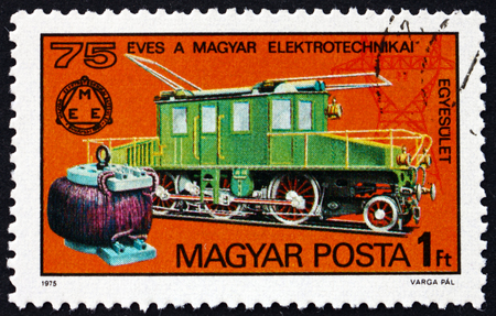 HUNGARY - CIRCA 1975: a stamp printed in Hungary shows early transformer, Kando locomotive, 1902, pylon, 75th anniversary of Hungarian Electrotechnical Association, circa 1975 Éditoriale