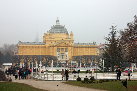 CROATIA ZAGREB, 18 DECEMBER 2016: Ice skating park in winter on King Tomislav square, located near the Art Pavilion, with visitors skating around the fountain, Zagreb, Croatia