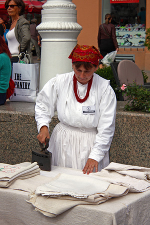 CROATIA ZAGREB  21 SEPTEMBER 2013: Woman, dressed in traditional clothes, is ironing her clothes, Croatia