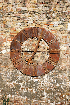 Old weathered clock on wall of the building
