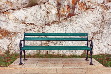 Wooden bench in front of the stone wall
