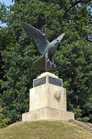 The falcon sculpture on the top of Mogila, an artifical hill in Maksimir park, Zagreb, a man running uphill