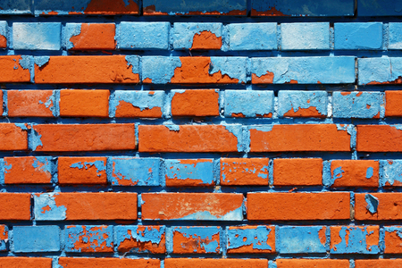 Old brick wall, old texture of red bricks with blue paint, closeup