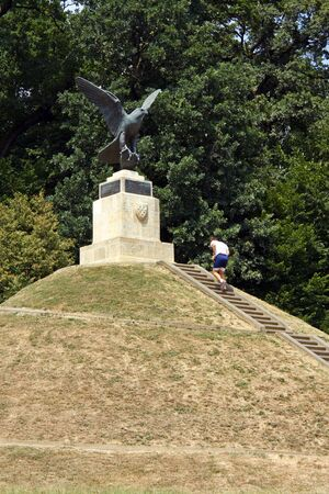 CROATIA ZAGREB, 15 JULY 2011: The falcon sculpture on the top of Mogila, an artifical hill in Maksimir park, Zagreb, a man running uphill