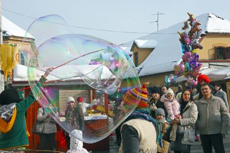 SAMOBOR, CROATIA - FEBRUARY 13, 2010: People at Samobor carnival create gigantic soap bubbles