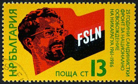 BULGARIA - CIRCA 1986: a stamp printed in Bulgaria shows Augusto Cesar Sandino (1893-1934), Nicaraguan revolutionary, and flag, Sandinista movement in Nicaragua, 25th anniversary, circa 1986 Editorial
