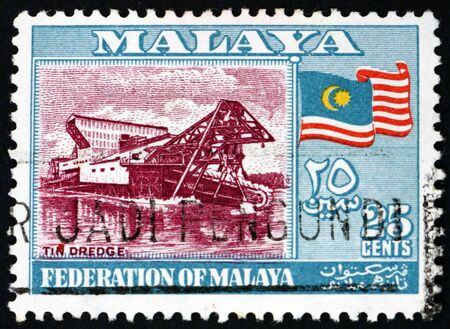MALAYA - CIRCA 1957: a stamp printed in Malaya shows tin dredge and flag, circa 1957