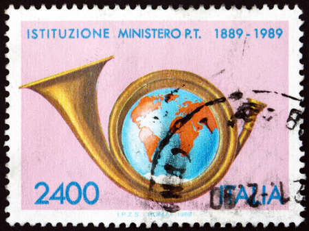 ITALY - CIRCA 1989: a stamp printed in Italy shows posthorn and Earth, centenary of Ministry of posts, circa 1989