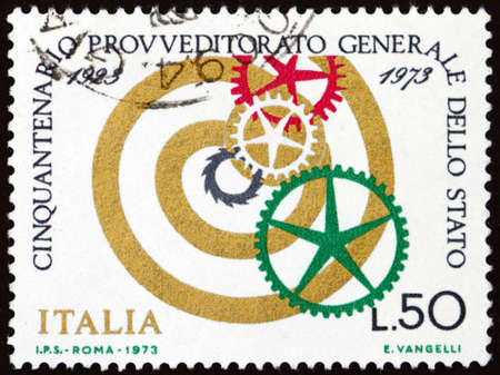 ITALY - CIRCA 1973: a stamp printed in Italy shows spiral and cogwheels, 50th anniversary of the State Supply Office, circa 1973