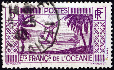 FRENCH POLYNESIA - CIRCA 1934: a stamp printed in French Polynesia shows spear fishing, circa 1934 版權商用圖片