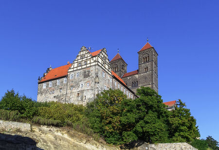 settles: Castle in Quedlinburg settles down on the mountain and towers over the city, Germany.